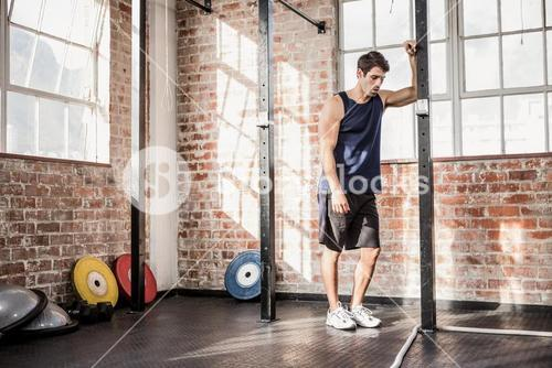 Man leaning on a pole