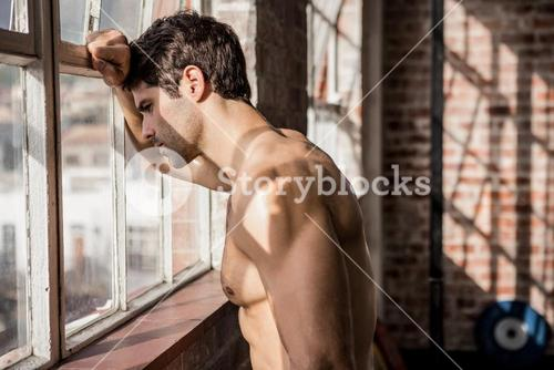 Shirtless man looking outside window