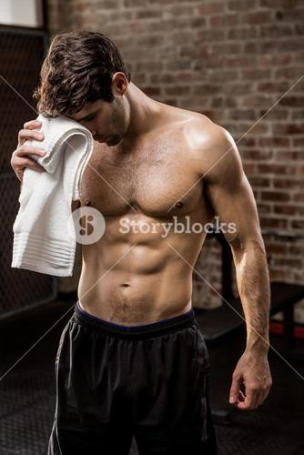 Muscular man wiping his face with towel
