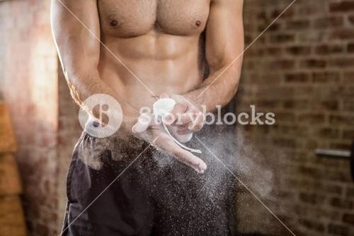 Midsection of muscular man applying chalk powder