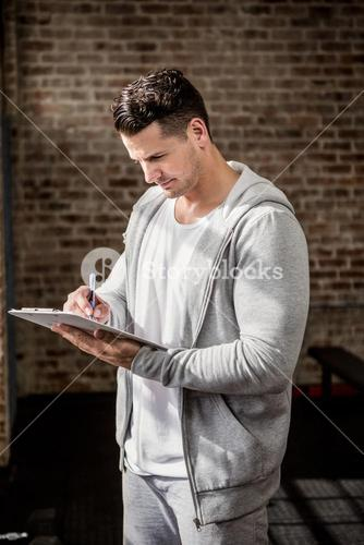 Muscular man writing on clipboard