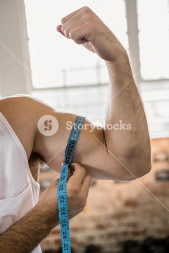 Man measuring biceps with tape