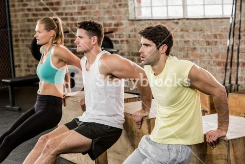 Cropped image of people holding plyo box and exercising