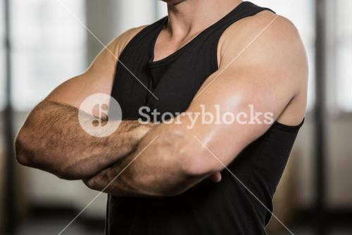 Midsection of man with arms crossed