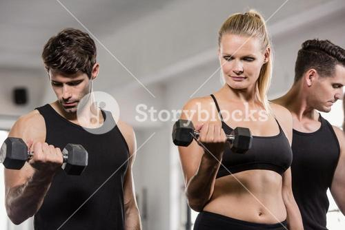 Serious people lifting barbell