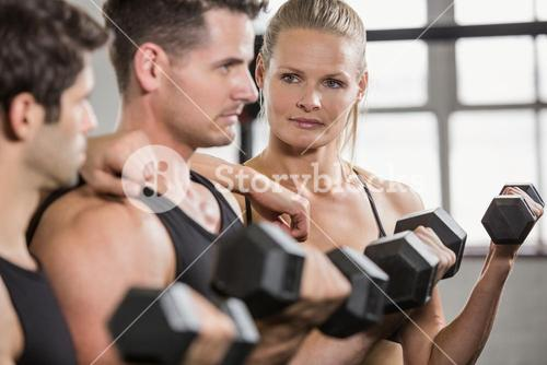 Focused people lifting dumbbell