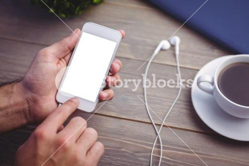 Person holding smart phone at desk