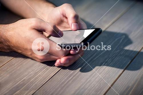 Person using smart phone at desk
