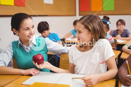 Pupil offering an apple to teacher