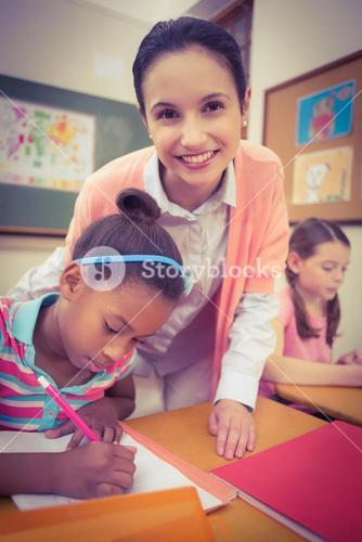 Pupil and teacher at desk in classroom