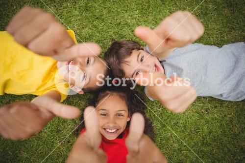 Cute pupils lying on grass smiling