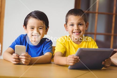 Cute pupils in class using phone and tablet