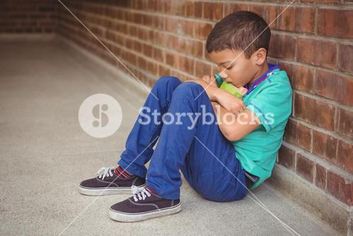 Upset lonely child sitting by himself