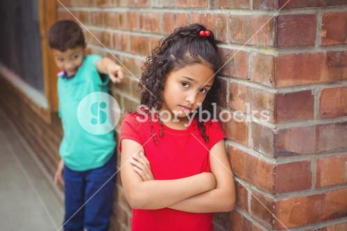 Upset child being teased by another child