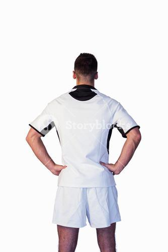 Rear view of a rugby player with hands on waist