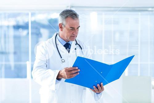 Male doctor reading document in hospital
