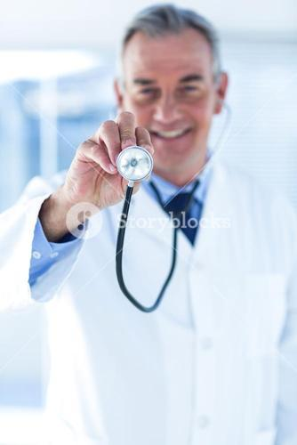 Smiling male doctor examining with stethoscope