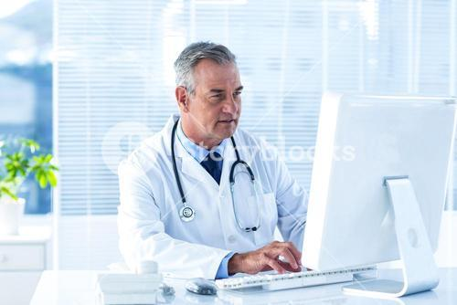 Male doctor using computer in hospital
