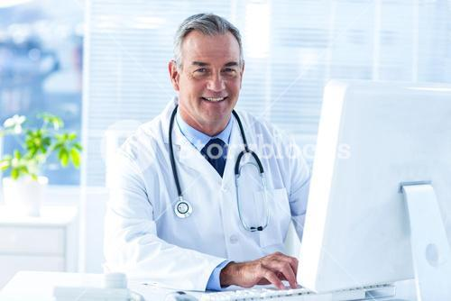 Smiling male doctor using computer in clinic