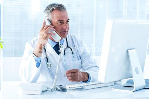 Male doctor holding telephone while looking at computer in hospital