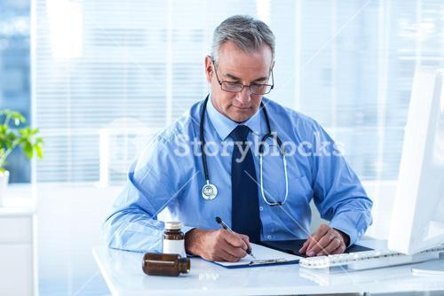 Male doctor writing prescription in hospital