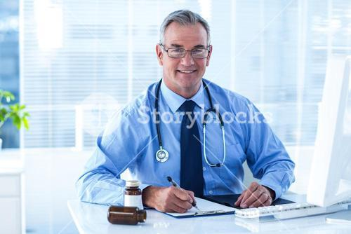 Portrait of smiling male doctor writing on document in clinic