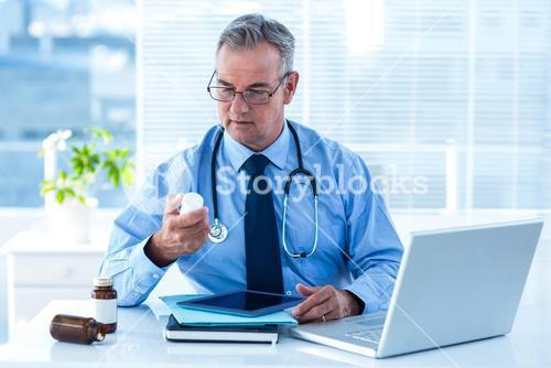 Male doctor holding pill bottle in clinic