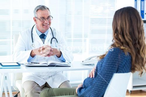 Male doctor discussing with pregnant woman in clinic