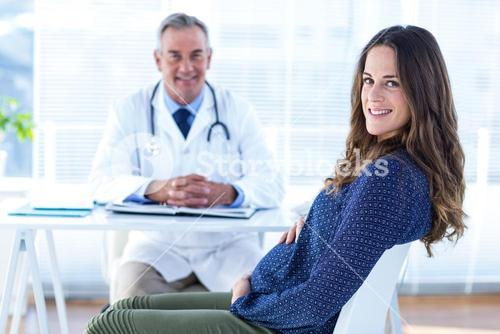 Portrait of pregnant woman with male doctor in clinic