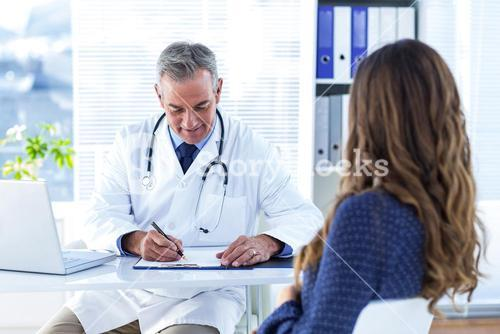 Male doctor writing prescription for woman in hospital