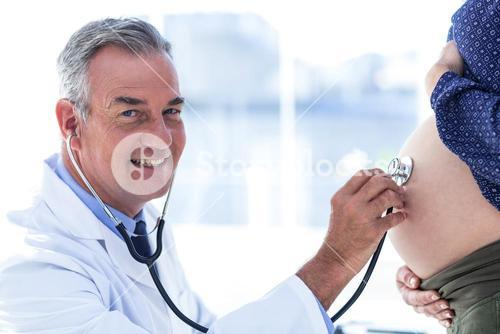 Portrait of male doctor examining pregnant woman in clinic