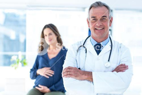 Portrait of smiling doctor with pregnant woman at clinic