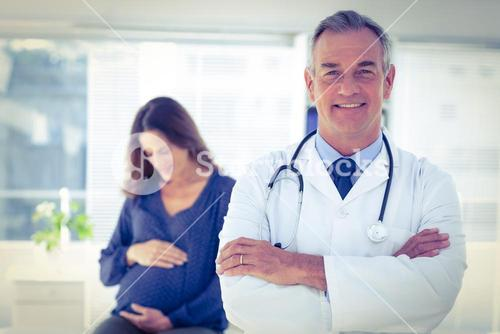 Portrait of male doctor with pregnant woman at clinic