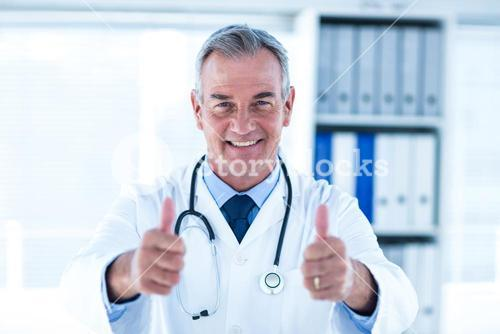 Portrait of doctor showing thumps up sign in clinic