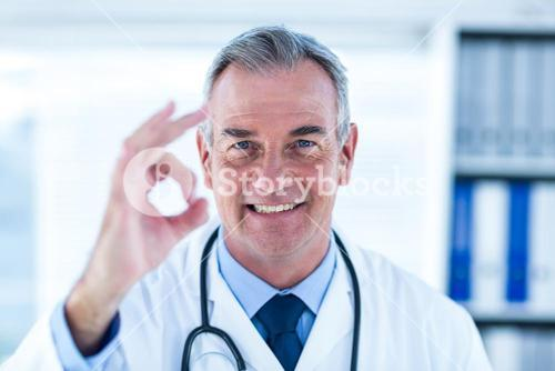 Portrait of male doctor showing ok sign in clinic