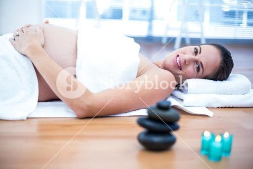 Pregnant woman touching belly in spa