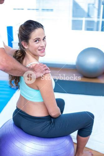 Happy pregnant woman having relaxing massage at gym