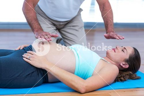 Therapist performing reiki on patient