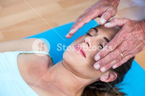 Relaxed woman getting reiki treatment