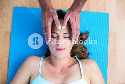 Overhead view of pregnant woman getting reiki treatment