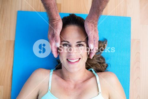 Portrait of smiling pregnant woman getting reiki treatment