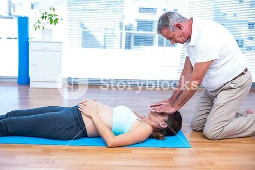 Therapist performing reiki on young woman