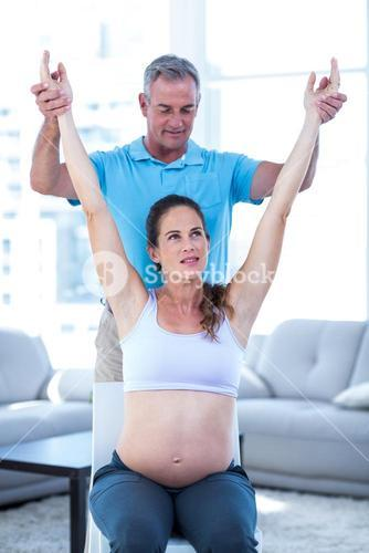 Instructor helping pregnant woman
