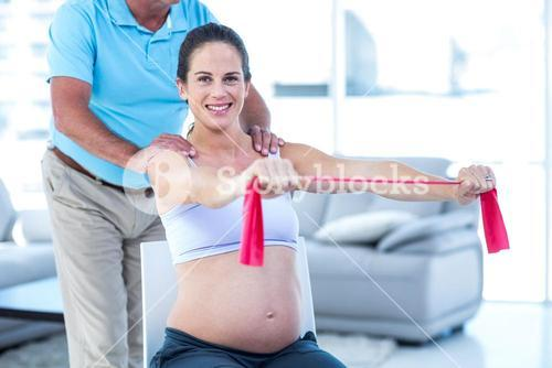 Portrait of smiling pregnant woman stretching exercise band
