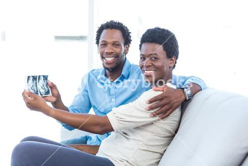 Happy couple showing photo at home