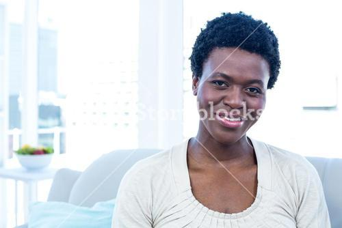 Happy woman sitting in living room