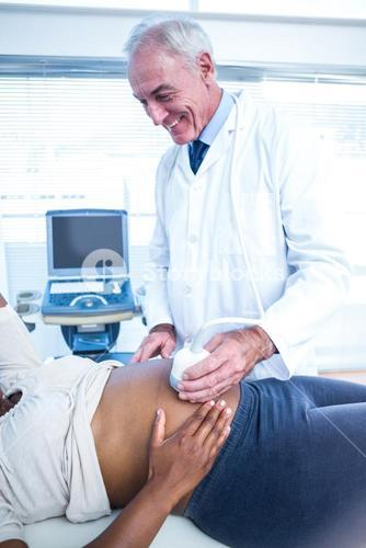 Smiling male doctor performing ultrasound on pregnant woman