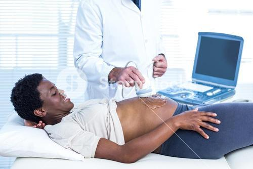 Happy pregnant woman looking at doctor