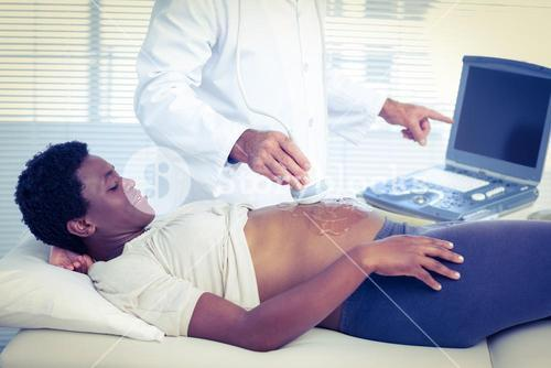 Doctor applying ultrasound gel on belly of woman