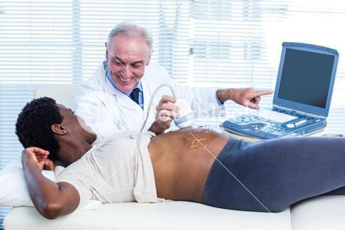 Smiling male doctor showing results on monitor